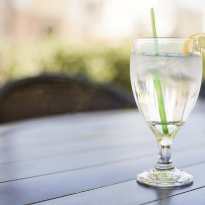 Glass of Iced Water with Lemon sits on Outside Table