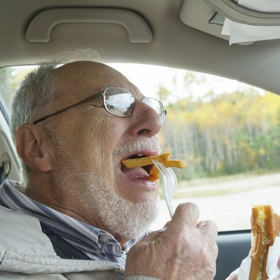 senior man with expressive face eating  fast foods