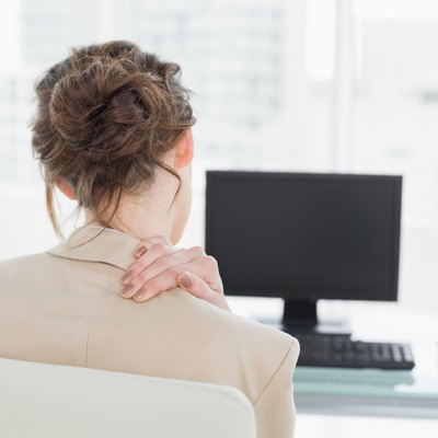 Rear view of businesswoman with neck pain in office