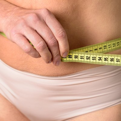 middle aged woman measuring her waist