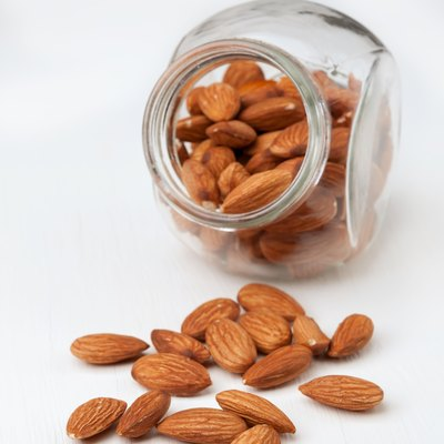 Almond nuts in a glass jar on white wooden background.