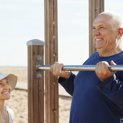 mature couple training with chin-up bar