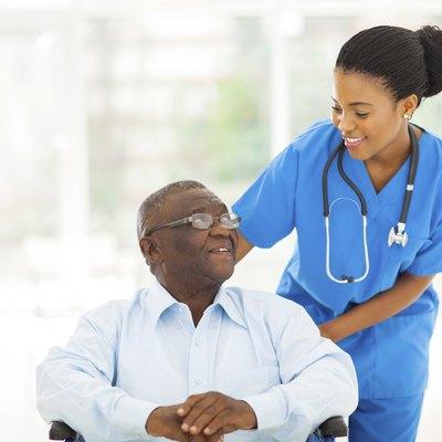 african nurse taking care of senior patient in wheelchair