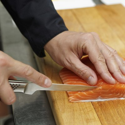 Chef is slicing salmon fillet