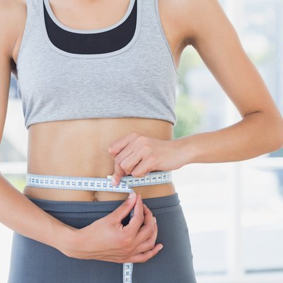 Mid section of a woman measuring waist in fitness studio