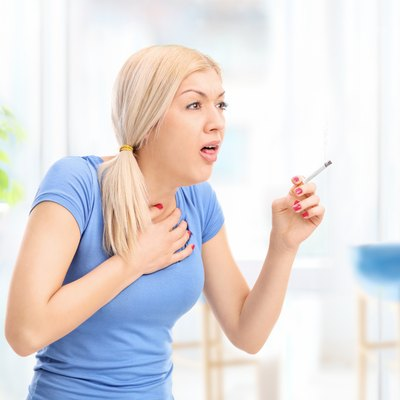 Young woman coughing from a cigarette