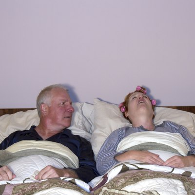 Man Looking Aghast at Wife in Bed