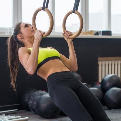Fit woman going pull-ups with gymnastic rings in gym.