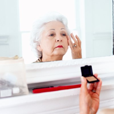 portrait of an elderly woman applying makeup