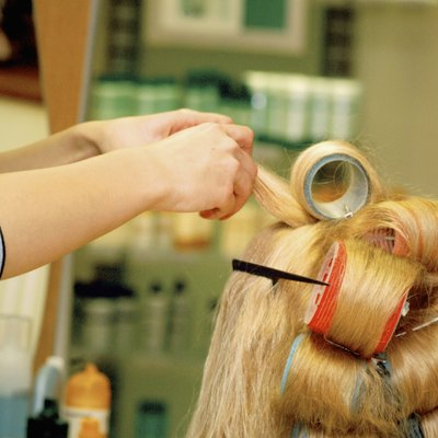 Close-up of a female hairdresser adjusting curlers in a mid adult woman's hair
