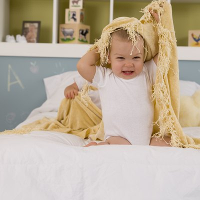 Child playing with blanket on bed