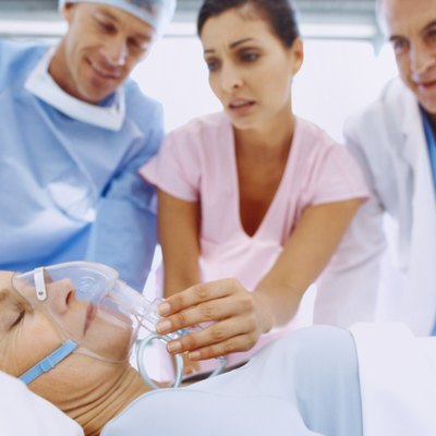 Close-up of hospital staff examining patient in bed