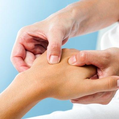 Therapist doing massage on female hand.