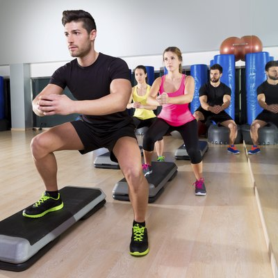 Cardio step dance squat group at fitness gym