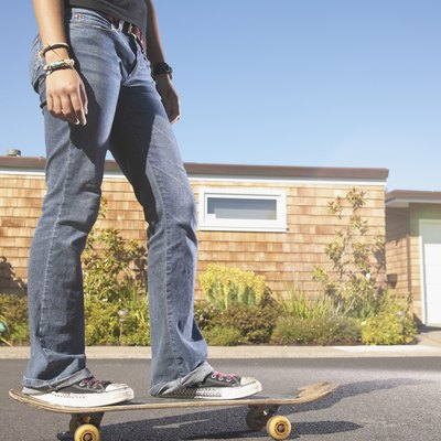 Low section view of a teenage girl skateboarding on the street