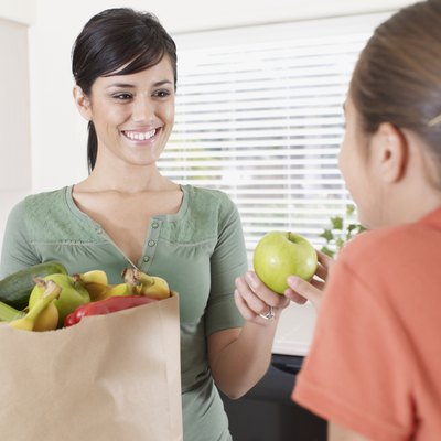 Woman handing young girl in kitchen an apple out of grocery bag and smiling