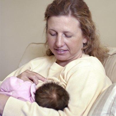 Woman nursing baby daughter