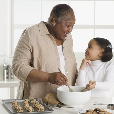 Senior woman making cookies with her granddaughter