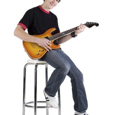 Teenage musician sitting on stool