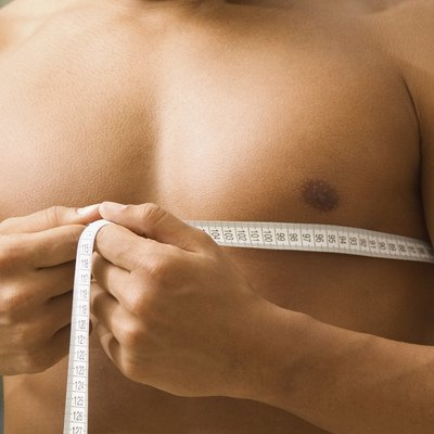 Young man measuring chest, close-up, part of