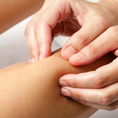 Detail of hands doing osteopathic massage on female calf muscle.
