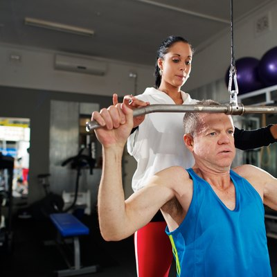 Man doing exercise in Gym with Personal Trainer