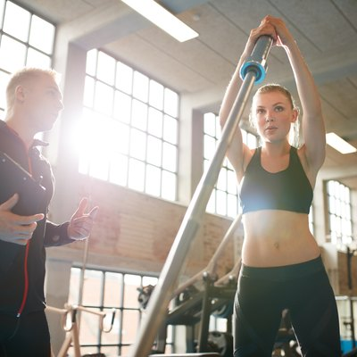 Woman exercising with trainer at fitness center