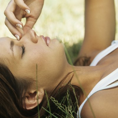Young woman lying on grass with eyes closed,rubbing nose,close-up,profile