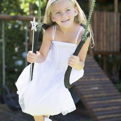Girl in fairy princess costume sitting in swing