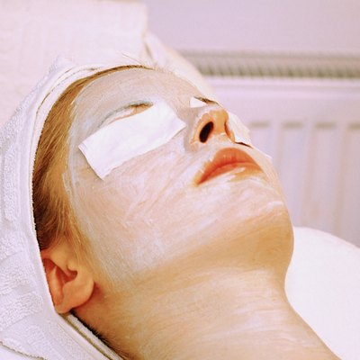Mid adult woman getting a facial mask