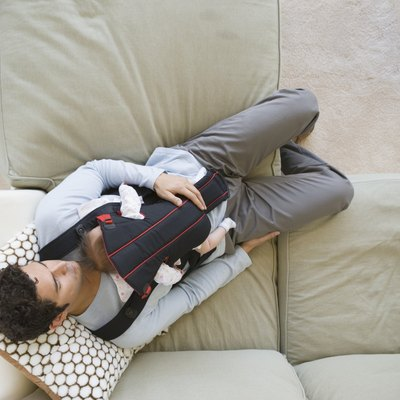 Hispanic father sleeping on sofa with baby