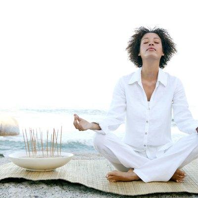 Woman meditating by ocean