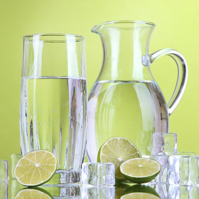 Glass pitcher of water   on green background