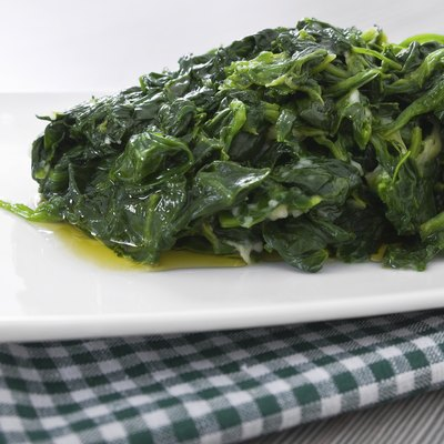 Boiled spinach on white dish.