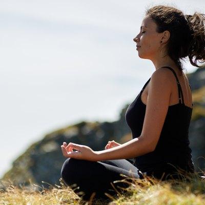 Woman practicing yoga on mountain
