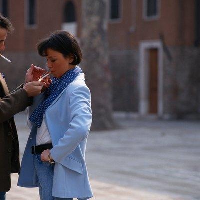 Man lighting woman's cigarette in street