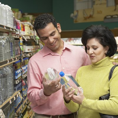 Mid adult couple holding bottles of mineral water in a supermarket