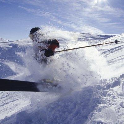 Skier landing in deep snow in mountains