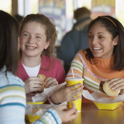 Three teenage girls sitting at a table and eating