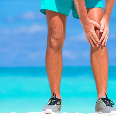 Male athlete suffering from pain in leg while exercising