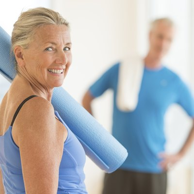 Smiling Woman With Exercise Mat At Home