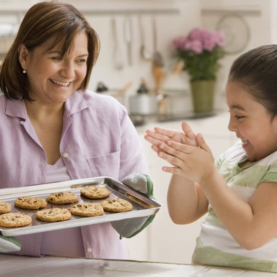 Hispanic mother and daughter with tray of cookies