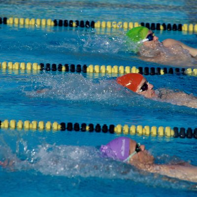 Three male swimmers in a race