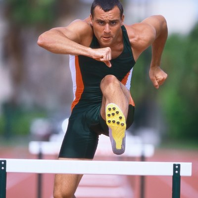 portrait of a young male athlete jumping hurdles