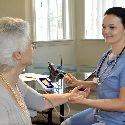 young nurse measuring the patients blood pressure
