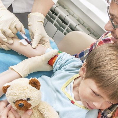 Collecting a blood from a vein from the kid.