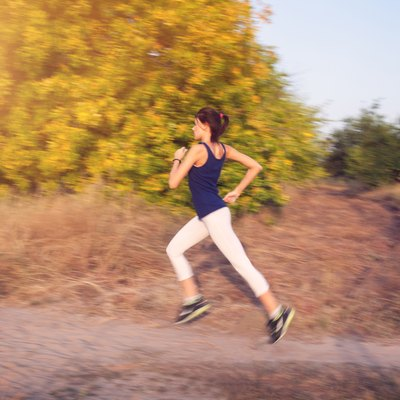 Young woman running on a rural road  in autumn forest