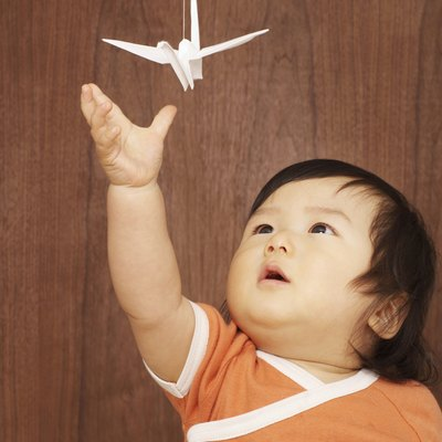 Baby girl (9-12 months) reaching for origami crane hanging from string, close-up
