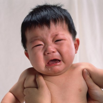 Baby boy is lifted, crying, portrait, front view
