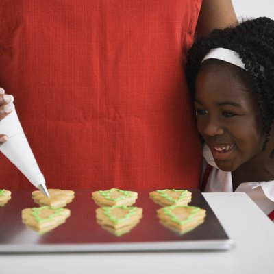 African girl watching mother decorate cookies